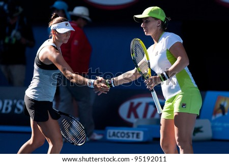 MELBOURNE - JANUARY 27: Svetlana Kuznetsova (R) and Vera Zvonareva of Russia winning the doubles championship at the 2012 Australian Open on January 27, 2012 in Melbourne, Australia. - stock photo
