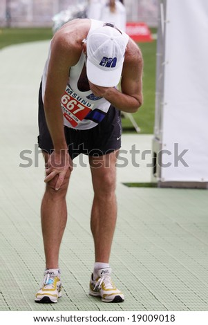 MELBOURNE - OCTOBER 12: An exhausted competitor completes the Melbourne marathon October 12, 2008. - stock photo
