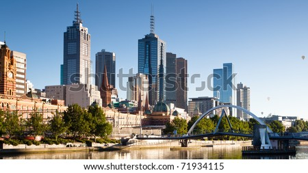 Melbourne skyline and the Yarra Footbridge leading to Flinders Street Station - stock photo