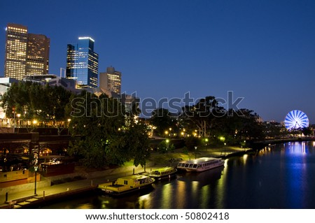 Melbourne skyline on yarra river at night with reflection in the water and the colorful ferris wheel. - stock photo