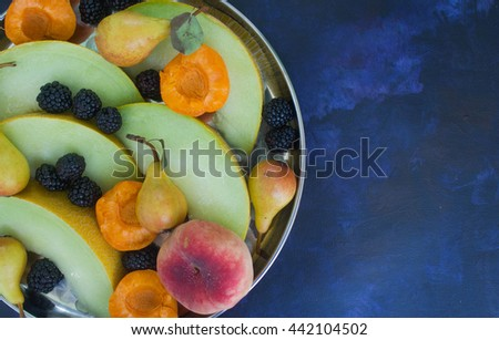 Melon, blackberries, peaches and pears on a dark background - stock photo
