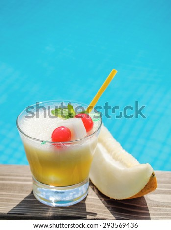 Melon cocktail on a pool side with a slice of melon - stock photo
