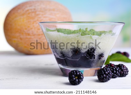 Melon smoothie in glass bowl on table on bright background