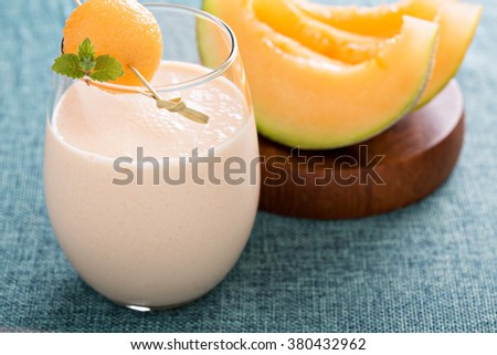 Melon smoothie on a table with light blue linen - stock photo