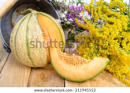 melon with a bouquet of yellow flowers on wooden table - stock photo