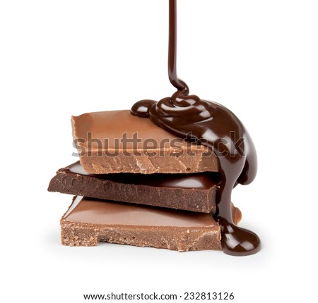 melted chocolate is poured on a stack of milk and dark chocolate - stock photo