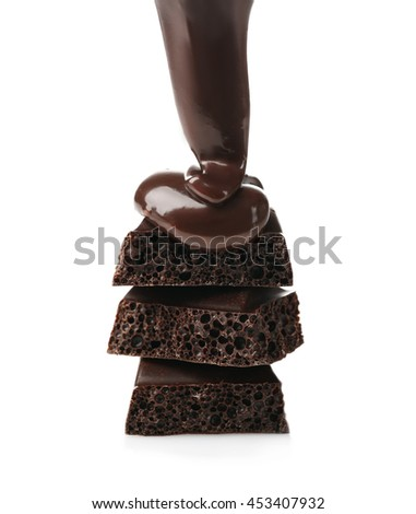 Melted chocolate pouring on chocolate bar, isolated on white - stock photo