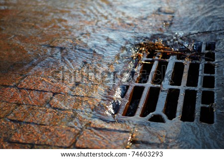Melted water flows down through the manhole cover on a sunny spring day - stock photo