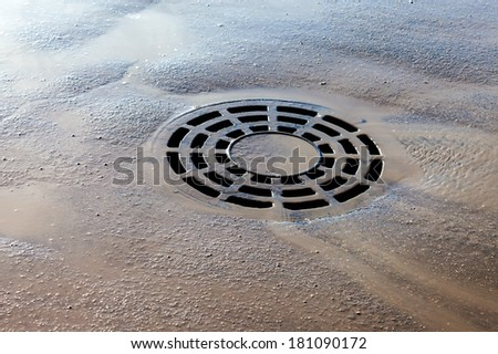 Melted water flows down through the manhole cover on spring day - stock photo