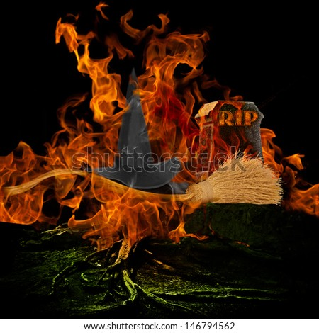 Melted Wicked Witch Is Dead Hat Broom Stick Spooky Scary Graveyard Burning Fire Flames Engulfing Grave Stone Rest In Peace RIP Evil Haunted Halloween Holiday Background Orange Glowing Light Tree Roots - stock photo