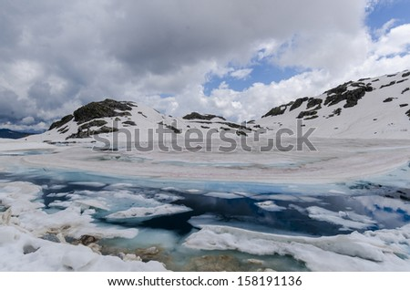 Melting glacier and the lake of clear blue water at an altitude of 2400 meters in the Alps