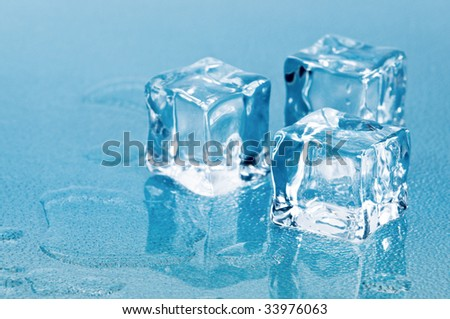 Melting ice cubes in pool of water on blue frosted glass - stock photo