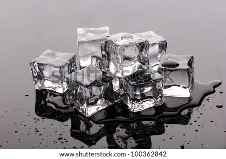 Melting ice cubes on grey background - stock photo