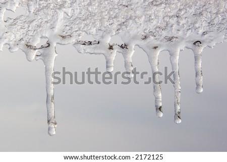 Melting ice drips refrozen - stock photo