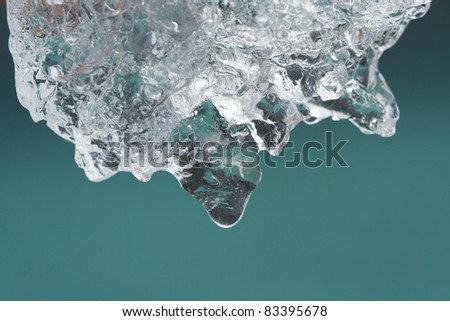 Melting ice from glacier with water drop over color of mountain lake. (Heating , clean drinking water concept) - stock photo