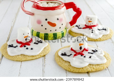 Melting snowman sugar cookies sitting on white wooden table with snowman mug filled with hot chocolate and marshmallows