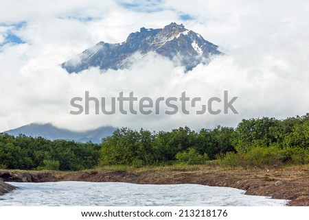 Melting snows and top of volcanic cone Koryaksky in the clouds - Kamchatka, Russia - stock photo