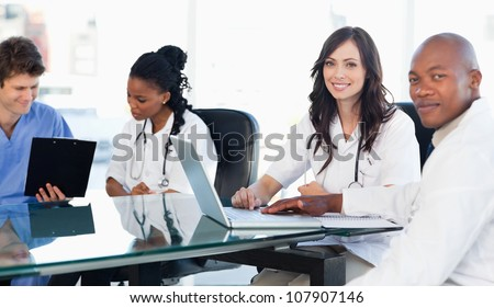 Members of a medical team looking at the camera while working on a laptop - stock photo