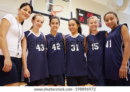 Members Of Female High School Basketball Team With Coach - stock photo