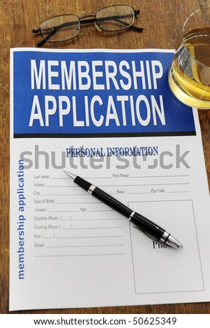 membership application form on a desk with a glass of whiskey