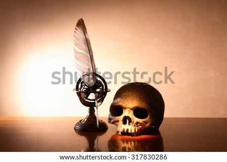 Memento Mori. Human skull on table near quill pen under beam of light - stock photo