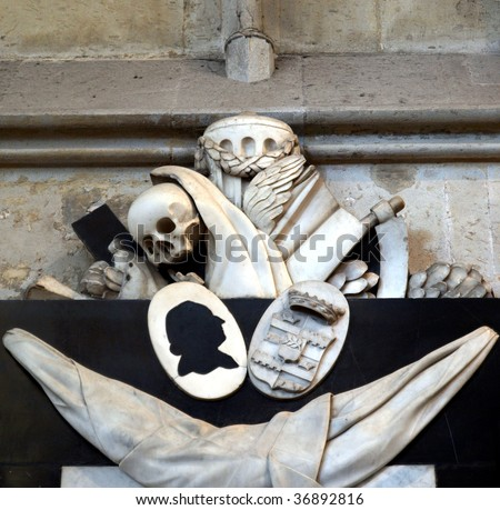 Memento mori (Remember thou shalt die) - Ancient medieval sculpture with skull and reaper's sickle in Koelner Dom cathedral, Koeln, Germany - stock photo