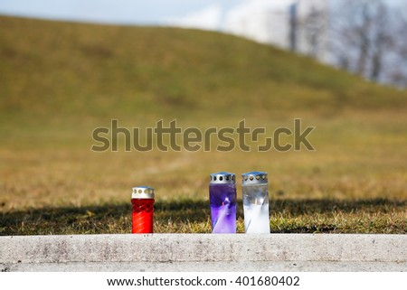 Memorial candles burning on the edge of an ashes scattering field in the graveyard. Death, passing, remembrance, funeral, sympathy and Day of the dead concept.   - stock photo