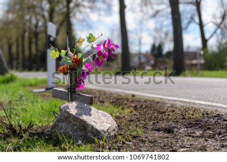 Memorial cross with flowers at the scene of an accident at the roadside
