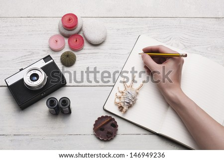 Memories, ideas & plans. Group of objects on white hardwood table. Hand writing on a blank paper. Studio shot. - stock photo