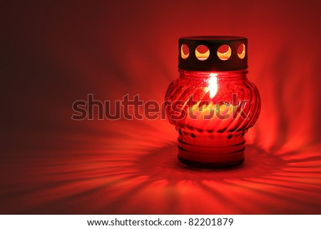Memory lantern with burning candle in the dark - stock photo