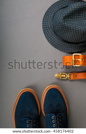 Men accessory, outfit. Black fedora hat, brown belt, suede shoes on the grey background. Top view, copy space, frame. Wedding.