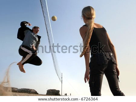 Men and a girl playing volleyball on a beach - stock photo