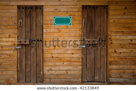Men and Woman Outdoor Toilet Wooden Doors - stock photo