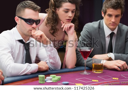 Men and woman sitting at poker table in casino - stock photo