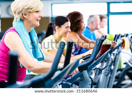 Men and women doing fitness spinning for sport, group of young and senior people - stock photo