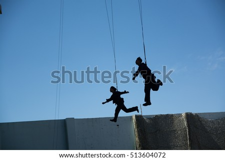 Men and women flying in sky with safety rope. Stunt who fly on sky background.