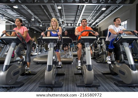 Men and women riding exercise bikes in health club - stock photo