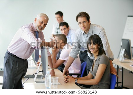 Men and women sitting at a desk in front of a desktop computer - stock photo