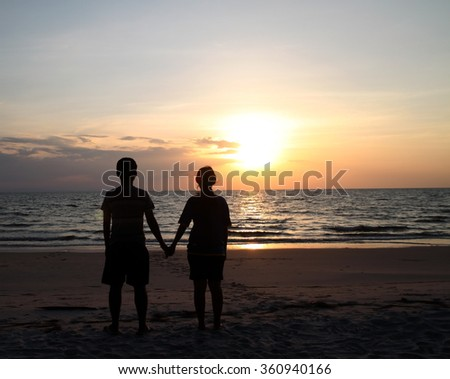 Men and women stand hand in hand to watch the sunset . - stock photo