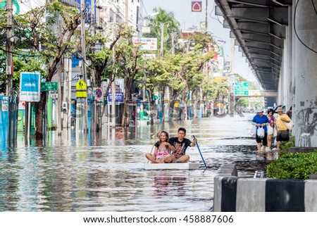 Men and women use a large sponge instead of a boat on road filled with water.This occurs when severe flooding in Thailand,A.D.2011. Shoot 02.01 PM. 09.Nov.2011  Bangkok,Thailand. - stock photo
