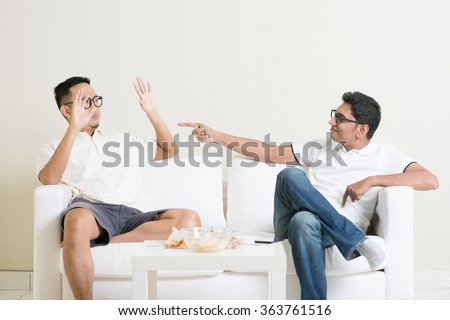 Men arguing. Two young male friend having argument at home. Multiracial people friendship.