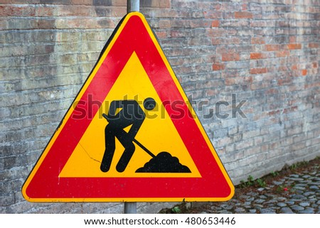 men at work, traffic sign on a brick wall