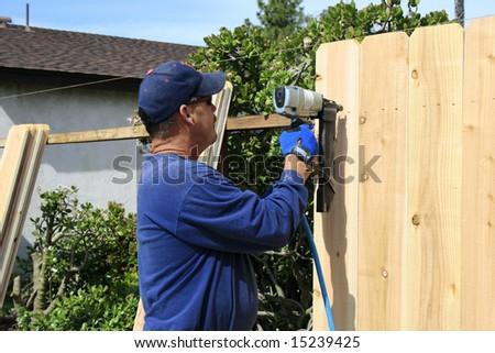 Men building a Fence in garden - stock photo