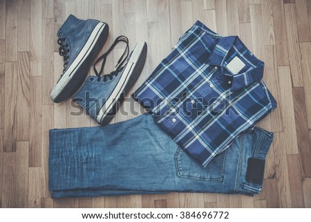 men casual outfit background, worn blue jeans, sneakers and plaid shirt - stock photo