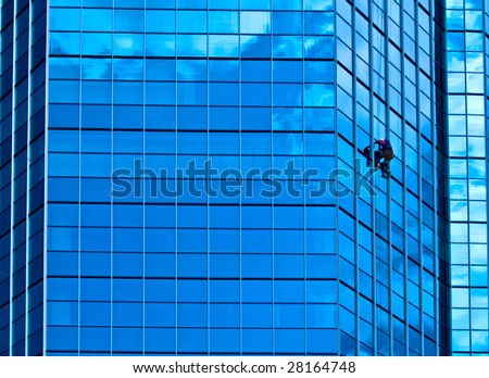Men cleaning the windows on a modern glass building - stock photo
