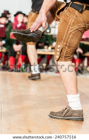 Men dressed in leather trousers is doing the traditional austrian folk dance - stock photo