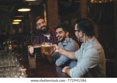 Men drink beer in a pub.