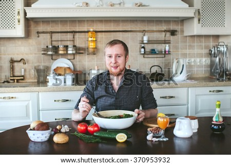 Men eating vegetarian salad in the kitchen - stock photo