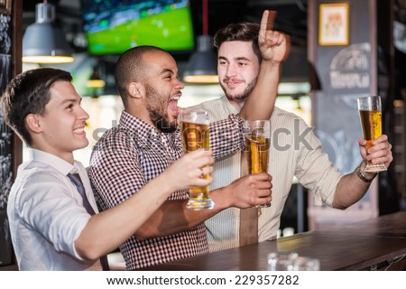 Men fans screaming and watching football on TV and drink beer. Three other men drinking beer and having fun together in the bar while there is a football game on TV - stock photo
