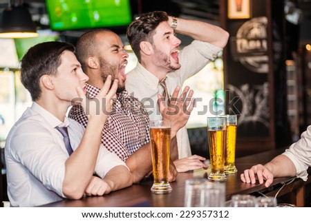 Men fans watching football on TV and drink beer. Three other men drinking beer and having fun together in the bar until the bartender communicates with them - stock photo